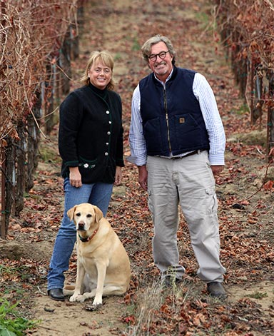 Debra Mathy with her husband and dog in one of Dutcher Crossing's vineyards